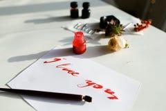 与红色题字的好的书法卡片我爱你在白色 免版税图库摄影