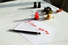 与红色题字的好的书法卡片我爱你在白色 免版税库存照片