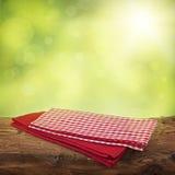 与红色餐巾的空的木桌 免版税库存图片