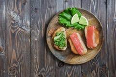与红色鱼和鲕梨,柠檬,莴苣的三明治,在一块木板材供食 顶视图 免版税库存图片