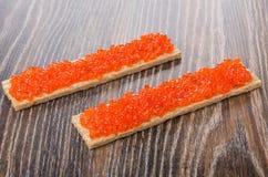 与红色鱼子酱的模仿的薄脆饼干在黑暗的桌上的 库存图片