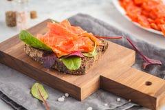与红色鱼鳟鱼和黑麦面包的新鲜的三明治在一条木蟒蛇 库存图片