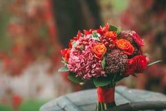 与红色,桔子和红葡萄酒玫瑰、莓果和其他绿色的土气婚礼花束在年迈的木日志 附庸风雅 免版税库存图片