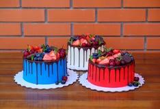 与红色,白色和蓝色奶油的三个蛋糕在桌上 库存照片