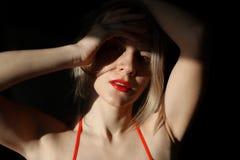 与红色嘴唇的沉思白肤金发的妇女特写镜头 免版税库存照片