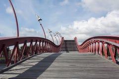 与红色细长立柱的弯曲的木楼梯在蓝天 库存照片