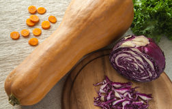 与红萝卜切片、新鲜的沙拉和紫色圆白菜的南瓜在一张木桌上 库存图片