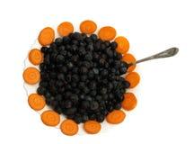 与红萝卜圆环的成熟黑莓在一个白色茶碟的有在白色背景隔绝的茶匙的 免版税库存图片