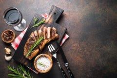 与红葡萄酒玻璃的烤牛肉striploin牛排 库存图片