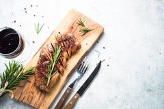 与红葡萄酒玻璃的烤牛肉striploin牛排 库存照片