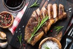 与红葡萄酒玻璃的烤牛肉striploin牛排 图库摄影