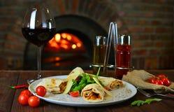 与红酒的鲜美意大利盘在有火木头的老地道餐馆 免版税库存照片