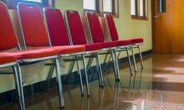 与红颜色的一把排队的椅子与石地板 免版税库存照片