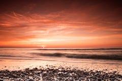 与红颜色的海滨在黄昏 免版税库存照片