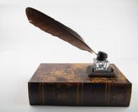 与纤管的古老墨水罐在老大型书本 库存图片