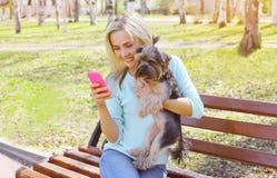 与约克夏狗狗的年轻微笑的女孩所有者 免版税库存照片