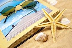与纪念品和壳的Photoalbum与沙子 免版税库存照片