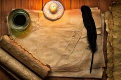 与纸和墨水的葡萄酒羽毛在根据蜡烛的桌上 库存图片