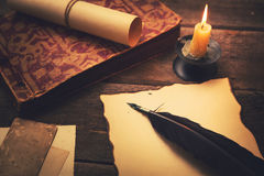 与纸和旧书的葡萄酒羽毛在桌上 免版税库存图片