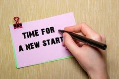 与纸夹的桃红色纸和妇女递拿着笔写 在黄色隔绝的对象 一个新的开始的时刻 图库摄影