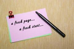 与纸夹的桃红色纸和妇女递拿着笔写 在黄色隔绝的对象 新页,一个崭新的开始 免版税库存图片