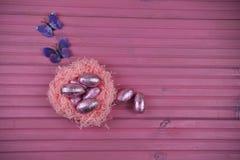 与纸巢的桃红色复活节装饰用发光的朱古力蛋和装饰填装了以蝴蝶的形式 库存图片