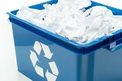 与纸张浪费的蓝色回收桶配件箱 库存照片