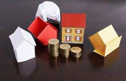 与纸房子和硬币堆的抵押贷款概念在woode 免版税库存图片