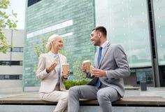 与纸杯的微笑的商人户外 免版税库存照片