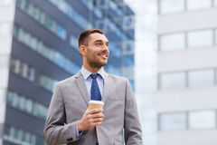 与纸杯的年轻微笑的商人户外 免版税库存照片
