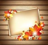 与纸板料的秋天叶子在木背景 图库摄影
