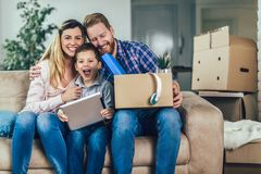 与纸板箱的家庭在新房里移动的天 免版税库存图片