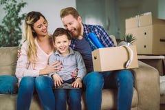 与纸板箱的家庭在新房里移动的天 图库摄影