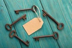 与纸标签的老生锈的钥匙在木板 库存图片