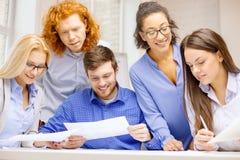 与纸的微笑的队在办公室 免版税库存照片