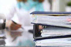 与纸的黏合剂等待处理与女实业家或秘书后面在迷离 国税局 免版税图库摄影