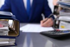 与纸的黏合剂等待处理与商人和秘书后面在迷离 会计计划预算 免版税库存图片