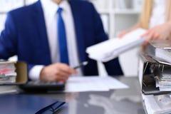 与纸的黏合剂等待处理与商人和秘书后面在迷离 会计计划预算 免版税图库摄影