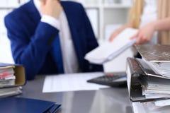 与纸的黏合剂等待处理与商人和秘书后面在迷离 会计计划预算 图库摄影
