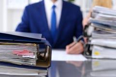 与纸的黏合剂等待处理与商人和秘书后面在迷离 会计计划预算 免版税库存照片