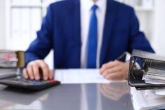 与纸的黏合剂等待处理与在迷离的商人后面 会计计划预算,审计 免版税图库摄影