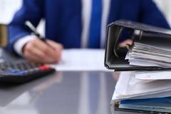 与纸的黏合剂等待处理与在迷离的商人后面 会计计划预算,审计 库存照片