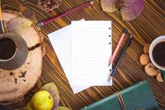 与纸笔记的,牛奶店, cofee, Ñ  ezve,秋叶的木背景 工作场所顶视图 免版税库存图片