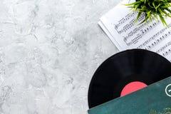 与纸笔记的Vynil纪录在dj或音乐家工作的音乐演播室在石背景顶视图大模型 免版税库存图片