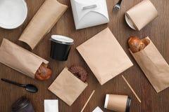 与纸袋和不同的外带的项目的平的被放置的构成在木背景 免版税库存图片