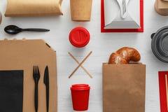 与纸袋的平的被放置的构成和在木背景的不同的外带的项目 库存照片