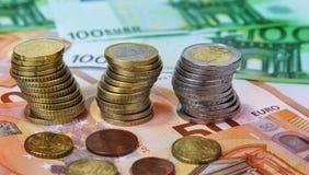 与纸钞票的被堆积的一枚和两枚欧洲硬币 免版税库存照片