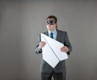 与纸飞机和风镜的商人 免版税图库摄影
