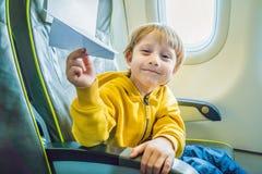 与纸飞机的小男孩戏剧在商业喷气机飞机飞行在度假 库存照片