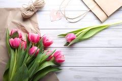 与纸,亚麻制串和购物袋的美丽的桃红色郁金香 免版税库存图片